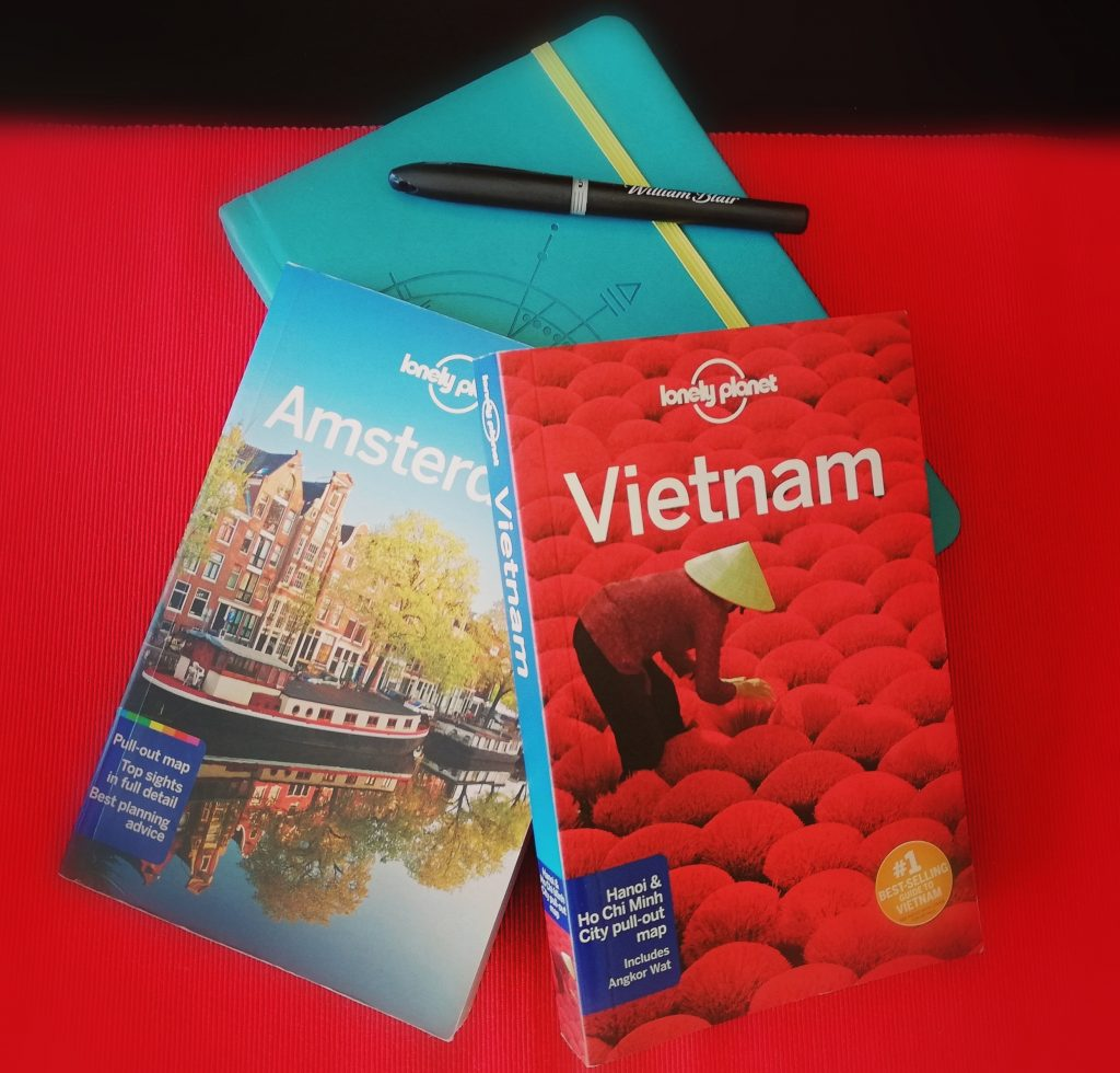 A picture depicting two Lonely Planet guides atop a red table runner