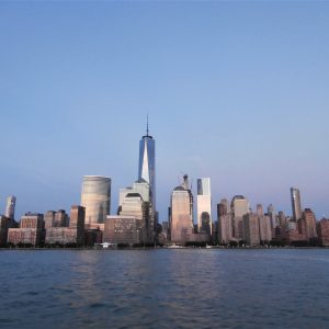 A picture taken atop a ferry depicting NYC skyline with the One World skycraper.