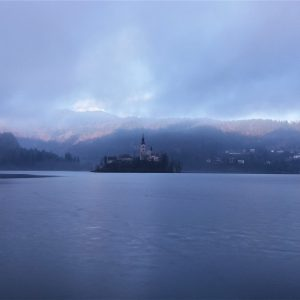 A picture of the church located on a small island in the middle of a half-frozen Lake Bled, in February