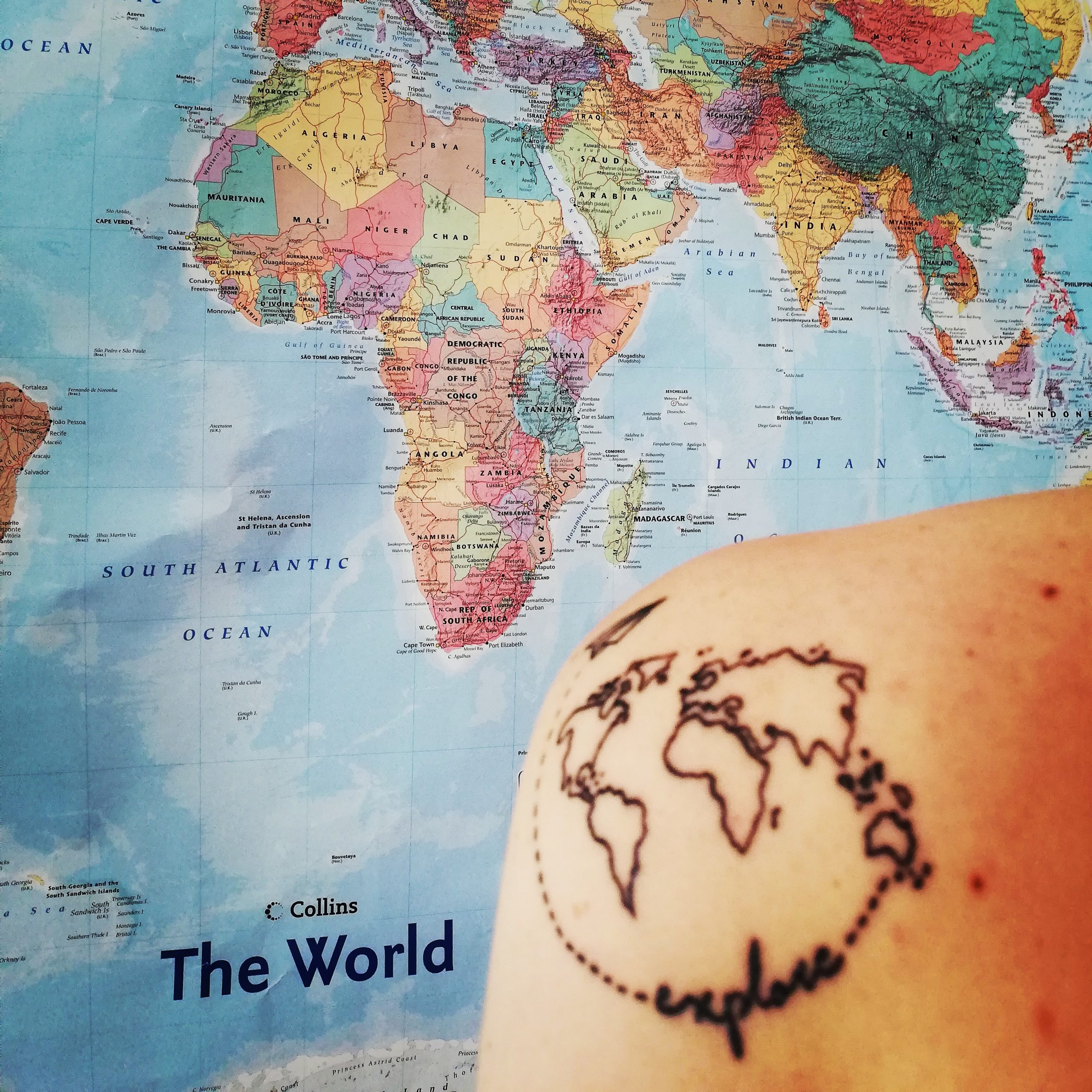 Departures Only logo depicting a tattoed shoulder in the foreground and a coloured world map in the background