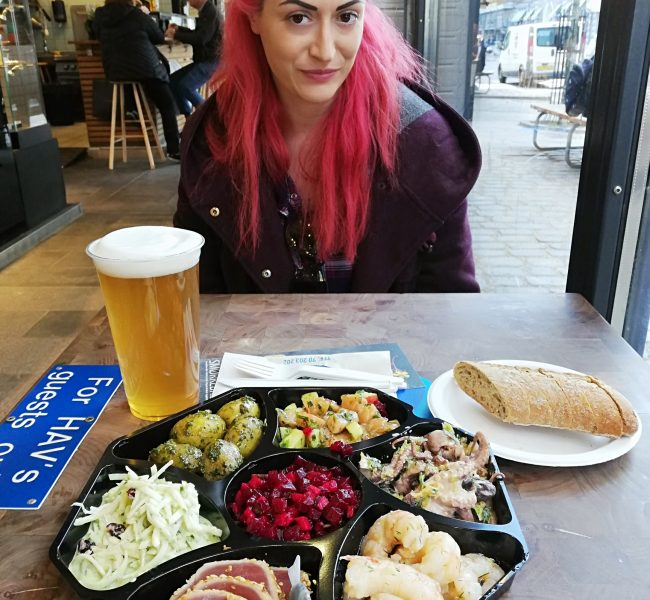 A picture of Claudia at Torvehallerne, Copenhagen sitting in front of a cold beer and a fish platter